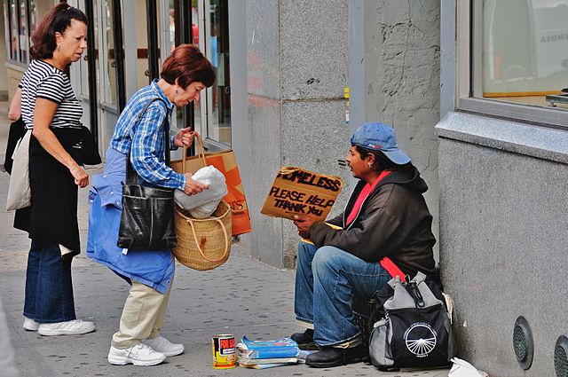 A photo of people donating money to a homeless man.