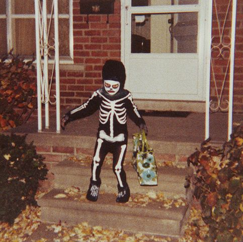 A child trick or treating in a skeleton costume.