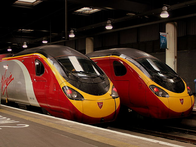 Virgin Branded trains side by side at station.